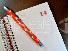 Calendar  with the February 14 date open and a pen