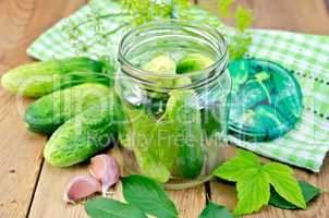 Cucumbers in jar with leaves and napkin on the board