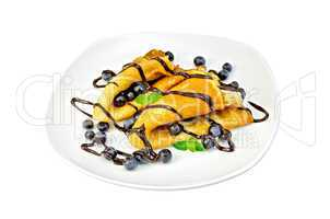 Pancakes with blueberries and chocolate in a plate