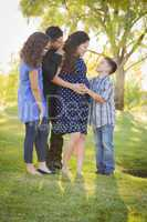 Happy Attractive Hispanic Family With Their Pregnant Mother Outd