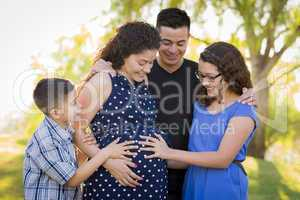 Hispanic Family Hands on Pregnant Mother Tummy Feeling Baby Kick