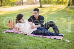 Pregnant Hispanic Couple with Piggy Bank on Belly in Park