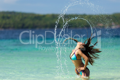woman flicking her long hair at the seaside
