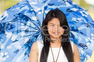 beautiful young thai girl under a blue sunshade
