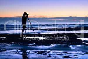 fotograf in der dämmerung am meer