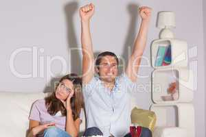 Excited man watching TV with wine by a bored woman at home