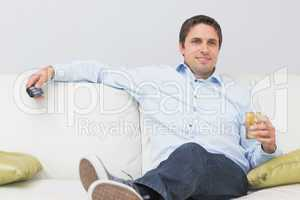 Relaxed man with a drink and remote control sitting on sofa at h