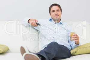 Man with a drink and remote control sitting on sofa at home