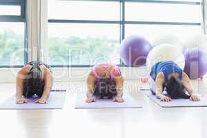 Fit women bending over on exercise mats in fitness studio