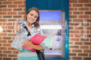 Pretty student standing showing her card to camera at the atm