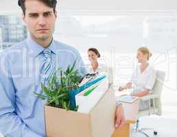 Businessman carrying his belongings with colleagues in backgroun