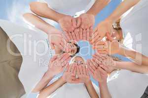 Happy volunteers with hands together against blue sky