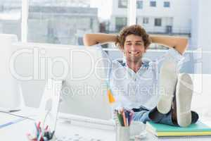 Relaxed casual man with legs on desk in bright office