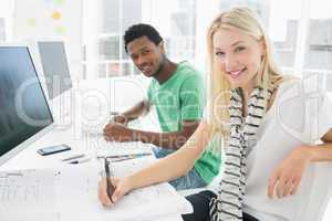 Artist drawing something on paper besides colleague at office