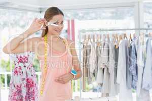 Beautiful female fashion designer holding scissors in store