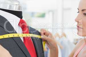 Close-up of a female fashion designer measuring suit on dummy