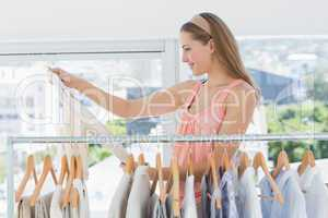 Female fashion designer looking at shirt by rack of clothes in s
