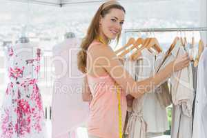 Beautiful female fashion designer with rack of clothes