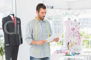 Fashion designer looking at sketch in the studio