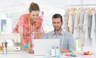 Fashion designers using laptop in bright studio