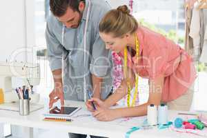 Fashion designers using digital tablet in bright studio