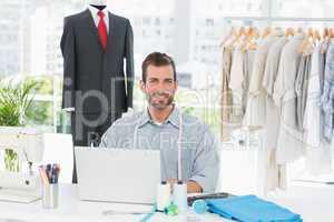 Smiling male fashion designer using laptop in studio