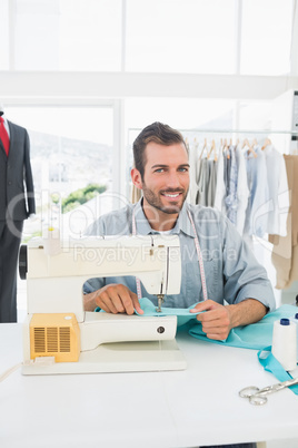 Smiling male tailor sewing in workshop