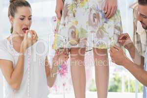 Two fashion designers adjusting dress on model
