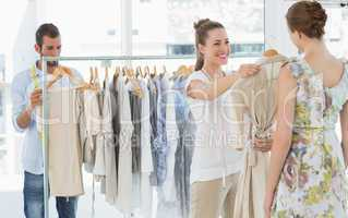 Seller helping shopper choose clothes in store