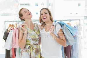 Cheerful women with shopping bags in the clothes store