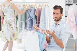 Bored man with shopping bags while woman by clothes rack