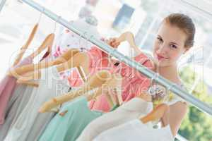 Happy female customer selecting clothes in store