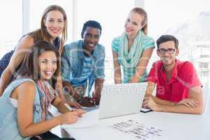 Young casual people using laptop in office