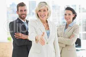 Confident businesswoman offering handshake with team