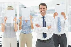 Businessman with colleagues holding blank paper in front of face