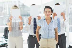 Businesswoman with colleagues holding blank paper in front of fa