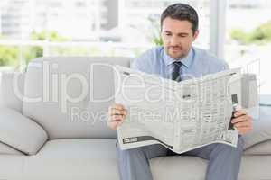 Well dressed man reading newspaper at home