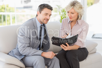Smart businessman and his secretary  looking at diary on sofa
