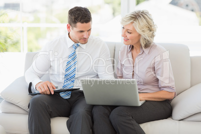 Smart businessman and his secretary with diary and laptop