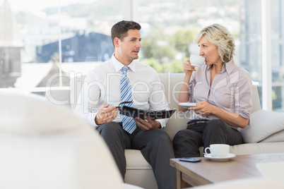 Smart businessman and his secretary  with diary and tea cup
