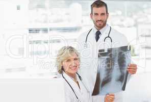 Female and male doctors with x-ray at medical office