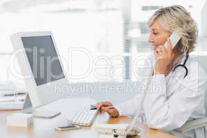 Female doctor using phone at desk in medical office