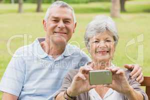 Cheerful senior couple photographing themselves at park