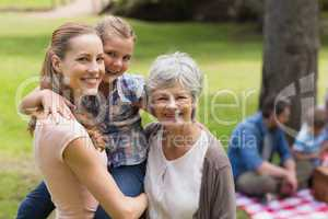 Grandmother, mother and daughter with family in background at pa