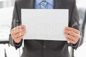 Businessman holding blank page