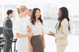 Businesswomen speaking together in conference room