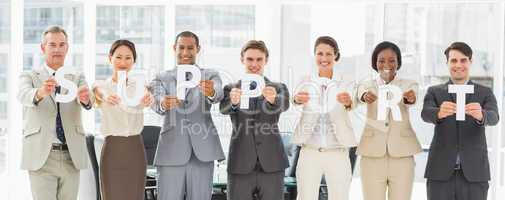 Diverse business team holding up letters spelling support