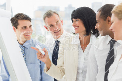 Colleagues watching happy businesswoman pointing to whiteboard