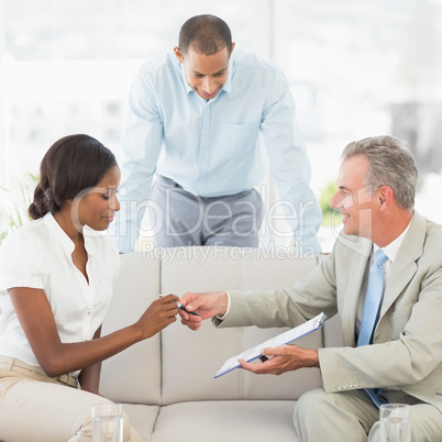 Salesman handing pen to client to sign the contract