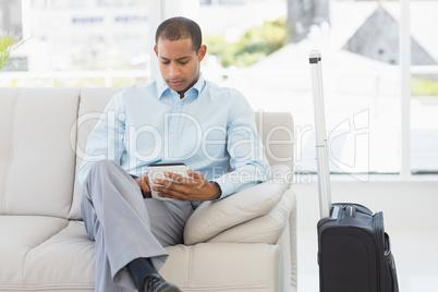 Man sitting on sofa waiting to depart on business trip